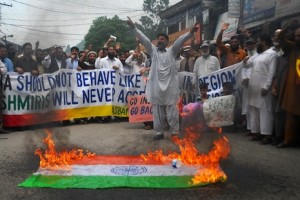 Indian Kashmiri refugees chant slogans beside a burning Indian flag during a protest against the visit of Indian Prime Minister Narendra Modi to Kashmir and strongly condemn his anti-Pakistan remarks, in Muzaffarabad, the capital of Pakistan-administered Kashmir on August 12, 2014. Narendra Modi accused Pakistan on August 12, 2014 of waging a proxy war in Kashmir as he became the first Indian prime minister in nine years to visit Kargil, scene of a deadly 1999 conflict with Pakistan.  AFP PHOTO/Sajjad QAYYUM